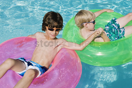 Children playing : Boys on float tubes in swimming pool