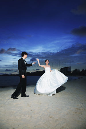 Arm raised : Bride and groom dancing on the beach