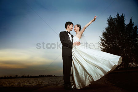 Smiling : Bride and groom posing outdoors