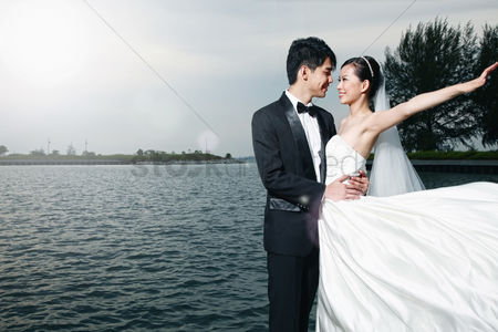 Arm raised : Bride and groom posing outdoors
