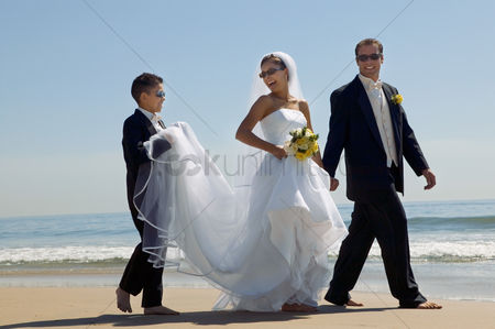Pre teen : Bride and groom with brother walking on beach