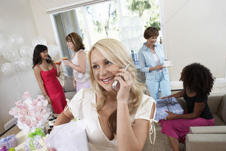 Celebrating : Bride talking on cell phone during bridal shower