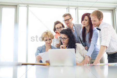 Window : Business colleagues with laptop analyzing document in creative office
