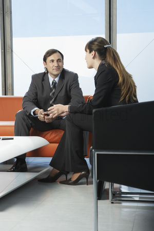 Business suit : Business man and woman talking in office waiting area