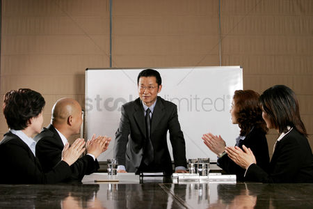 Sales person : Business man and women clapping their hands after a good presentation