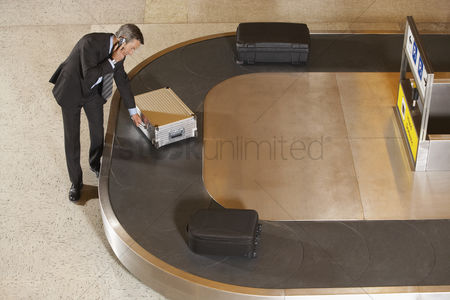 Selection : Business man claiming suitcase at luggage carousel in airport