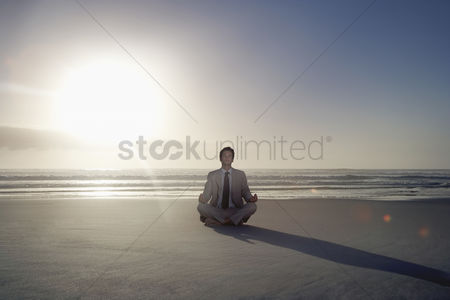 Contemplation : Business man sitting in lotus pose on beach