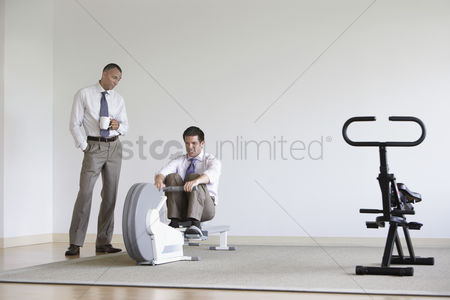 Pocket : Business man using rowing machine colleague standing by