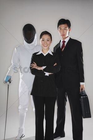 Fight : Business people and a man in fencing suit posing for the camera