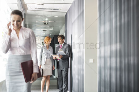 Cell phone : Business people discussing in corridor with colleague using cell phone in foreground
