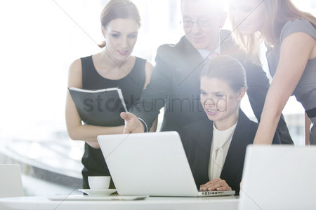 Office worker : Business people discussing over laptop in office cafeteria