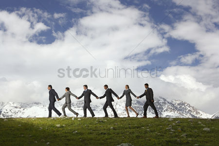 Ideas : Business people holding hands and walking through mountains side view