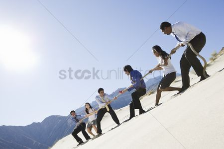 Business suit : Business people playing tug of war in the desert