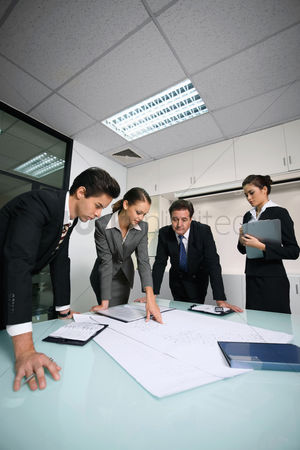 Leadership : Business people reviewing blueprints together