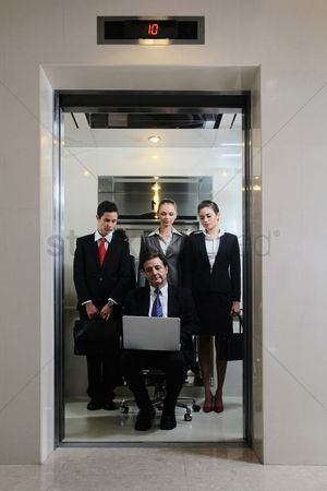 Portability : Business people watching businessman sitting on office chair and using laptop in an elevator