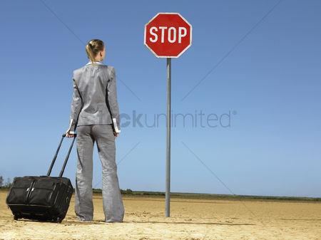Ponytail : Business woman with luggage standing in front of stop sign in desert back view