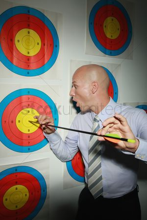 Amazed : Businessman admiring bull s-eye on taget