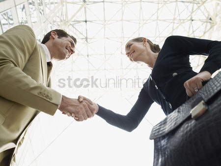 Business suit : Businessman and businesswoman shaking hands  low angle view