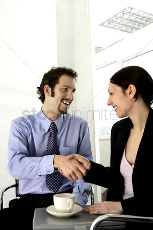Client : Businessman and businesswoman shaking hands