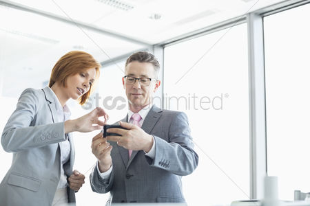 Cell phone : Businessman and businesswoman using cell people in office