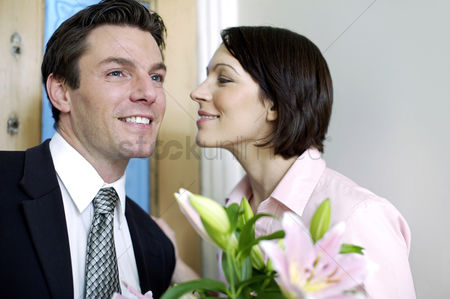Husband : Businessman bringing home a bouquet of flowers for his wife