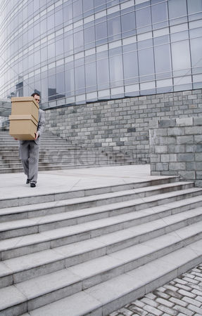 Stairs : Businessman carrying a stack of boxes down the stairs