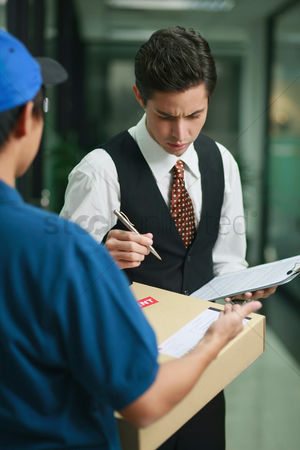 Frowning : Businessman checking before signing for package