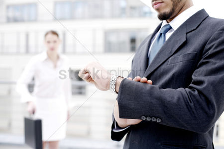Outdoor : Businessman checking the time on his watch