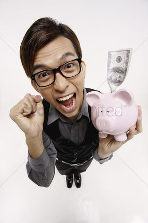 Celebrating : Businessman cheering while holding piggy bank with money