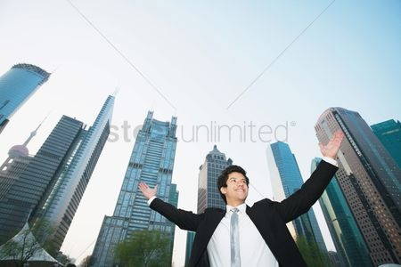 China : Businessman cheering with skyscrapers in the background