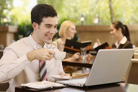 Satisfaction : Businessman drinking coffee while looking at laptop  businesswomen sitting in the background