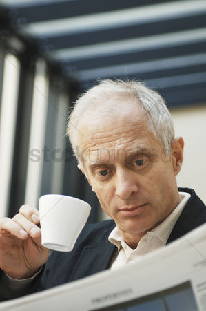 Determined : Businessman drinking coffee while reading newspaper