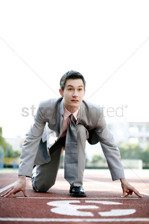 Motivation business : Businessman getting ready on the running track