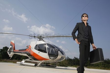 Pocket : Businessman holding briefcase walking away from helicopter