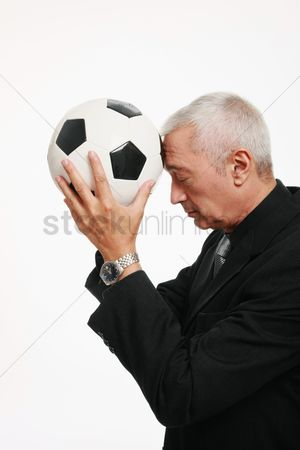Respect : Businessman holding football and praying