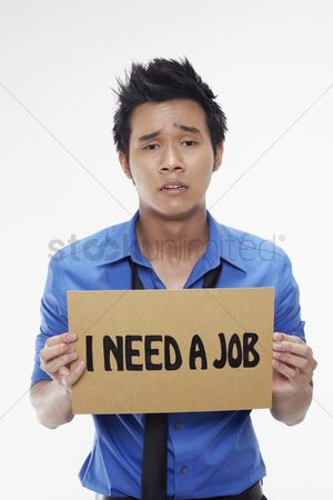 Frowning : Businessman holding  i need a job  sign