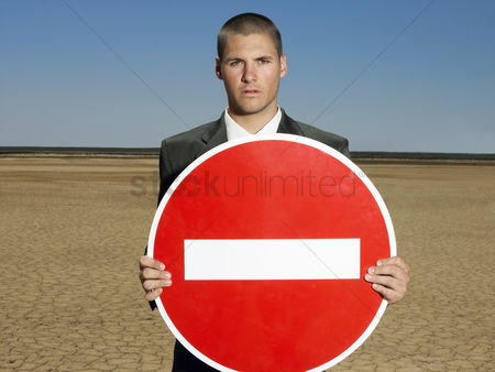 Forbidden : Businessman holding  no entry  sign in desert half length