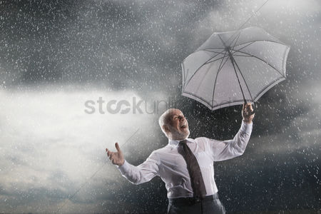 Bald : Businessman holding umbrella laughing in storm low angle view