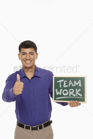 Motivation business : Businessman holding up a blackboard with  team work  written on it