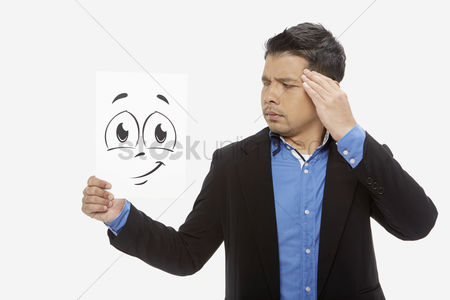 Frowning : Businessman holding up a smiley face doodle