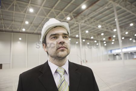 Spacious : Businessman in hard hat stands in brightly lit warehouse