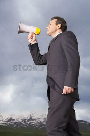 Moody : Businessman in mountain field speaking through megaphone low angle view