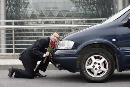 Kissing : Businessman kneeling and resting his head on a car while holding flowers