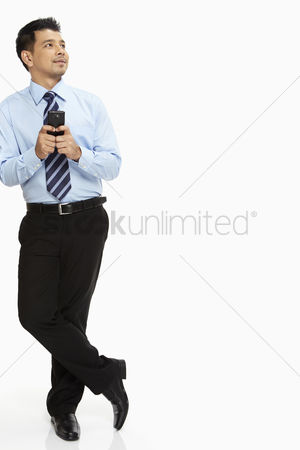 Portability : Businessman leaning against a wall  text messaging