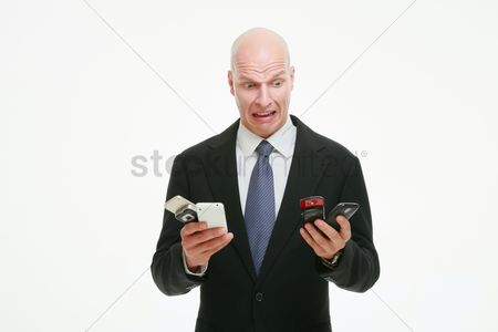 Bald : Businessman looking at all his mobile phones