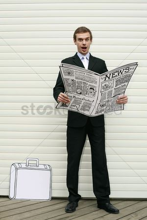 Cardboard cutout : Businessman looking shocked and holding newspaper