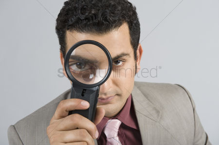 Magnifying glass : Businessman looking through a magnifying glass