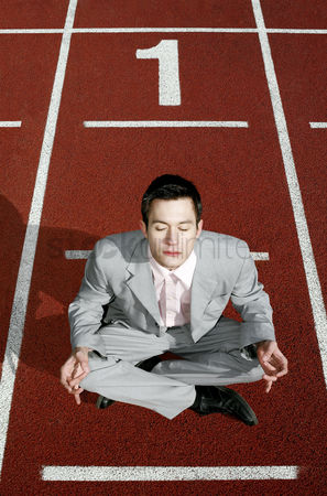 Practising yoga : Businessman meditating on a running track
