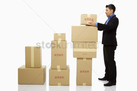 Malay : Businessman placing a box on top of a stack of boxes