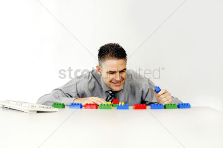 Employee : Businessman playing with plastic blocks